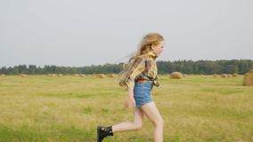 Teenager girl running on harvesting field on hay stack landscape in autumn village. Cheerful girl in jeans short and stock footage
