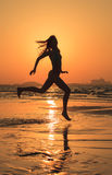 Teenager girl during running workout on the beach. Girl enjoying active running workout during sunset Stock Photos