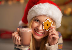 Teenager girl in santa hat with christmas cookie. Portrait of happy teenager girl in santa hat with christmas cookie and cup of hot chocolate Royalty Free Stock Photo