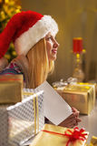 Teenager girl in santa hat with christmas postcard Royalty Free Stock Photography