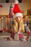 Teenager girl in santa hat having fun time. Happy teenager girl in santa hat having fun time in christmas decorated kitchen Royalty Free Stock Image