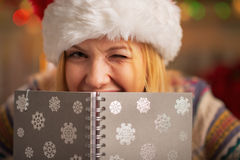 Teenager girl in santa hat hiding behind notepad Stock Photography
