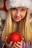Teenager girl in santa hat holding christmas ball Stock Image
