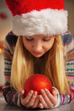 Teenager girl in santa hat holding christmas ball Stock Photos
