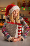 Teenager girl in santa hat hugging shopping bags Royalty Free Stock Photos