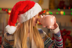 Teenager girl in santa hat with piggy bank Stock Image