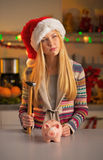 Teenager girl in santa hat with piggy bank Royalty Free Stock Photos