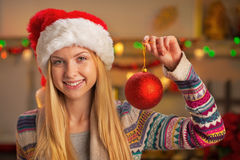 Teenager girl in santa hat showing christmas ball Stock Image