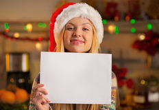 Teenager girl in santa hat showing paper sheet Stock Photos