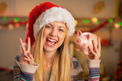 Teenager girl in santa hat showing piggy bank Stock Images