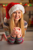 Teenager girl in santa hat showing piggy bank Stock Image