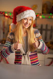 Teenager girl in santa hat showing thumbs up Stock Image