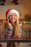 Teenager girl in santa hat talking cell phone Royalty Free Stock Images