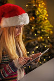 Teenager girl in santa hat using tablet pc Stock Photography