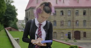 Teenager girl in school uniform with backpack writing and showing word start
