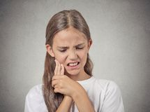Teenager girl with sensitive tooth ache. Closeup portrait young teenager girl with sensitive tooth ache, crown problem touching outside mouth with hand isolated royalty free stock image