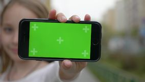 Teenager girl showing mobile phone with green screen to camera on city street. Close up girl teenager holding in hand. Front camera smartphone with green screen stock video footage