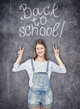 Teenager girl showing victory sign on the chalkboard background Stock Images