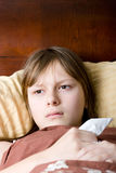 Teenager girl sick with flu lying in bed Royalty Free Stock Photo