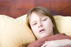 Teenager girl sick with flu lying in bed ill Royalty Free Stock Images