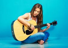 Teenager girl singer with guitar. Sitting on a floor Stock Images