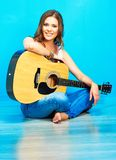 Teenager girl singer with guitar. Sitting on a floor royalty free stock photo