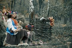 Teenager girl sitting in hay wearing a wreath and national Ukrainian costume next to the fruit basket royalty free stock images