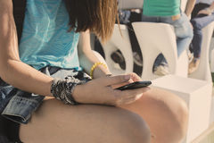 Teenager girl sitting with mobile phone in hand Stock Photo