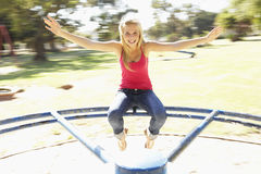 Teenager Girl Sitting On Playground Roundabout Royalty Free Stock Images