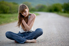 Teenager girl sitting on road royalty free stock photography