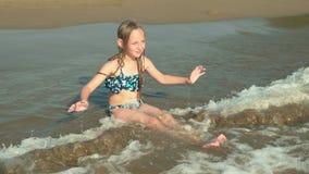 Teenager girl sitting on sea beach enjoying water waves. Happy tourist girl playing with sea waes on sandy beach. Teenager girl sitting on sea beach enjoying stock footage