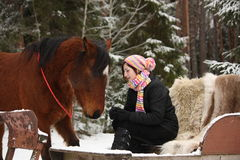 Teenager girl sitting in the sled with furs and brown horse Royalty Free Stock Photos