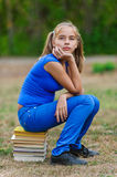 Teenager girl sitting on stack Stock Photos