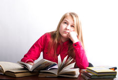 Teenager girl sitting at a table in front of her Stock Photos