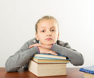 Teenager girl sitting at a table in front of her Royalty Free Stock Photography