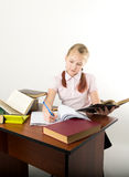 Teenager girl sitting at a table in front of her. Teenag girl sitting at a table in front of her large pile of books. schoolgirl reading a books and doing Royalty Free Stock Images