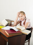 Teenager girl sitting at a table in front of her. Teenag girl sitting at a table in front of her large pile of books. schoolgirl reading a books and doing Stock Photography