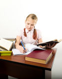 Teenager girl sitting at a table in front of her. Teenag girl sitting at a table in front of her large pile of books. schoolgirl reading a books and doing Royalty Free Stock Image