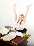 Teenager girl sitting at a table in front of her. Teenag girl sitting at a table in front of her large pile of books. schoolgirl reading a books and doing Stock Image