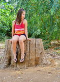Teenager girl sitting on a tree trunk. Teenager girl sitting on a sawed giant eucalyptus tree trunk in summer dress Royalty Free Stock Images