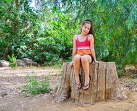 Teenager girl sitting on a tree trunk Stock Photo