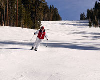 Teenager girl skier. Teenager girl skiying on a sunny day. White pants red coat Stock Image