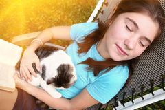 Teenager girl sleeping in chaise lounge with cat. And book close up portrait stock photos