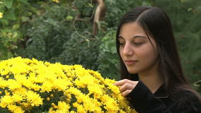 Teenager girl smelling flowers stock footage