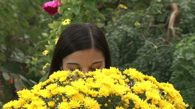 Teenager girl smelling flowers stock video footage