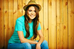 Teenager girl smiling with teeth seating against wood backgroun. D. Young woman portrait with hat in hipster style Royalty Free Stock Photography