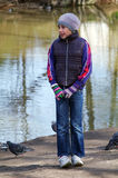 Teenager girl standing betwin pigeons birds on the shore of a pond Royalty Free Stock Photos