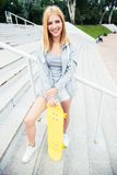 Teenager girl standing on stairs with skateboard Royalty Free Stock Image