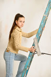 The teenager girl  on a step-ladder Stock Photography