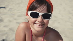 Teenager girl in sunglasses smile. Into camera on the beach stock footage